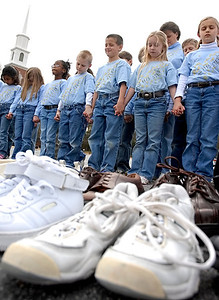 "2-15-08  --soles 4 souls 3--  Students and teachers at Eastside Christian School pray over the collected shoes before they are given to ""Soles 4 Souls"" to be distributed across the world.  The school collected over 1000 pairs of shoes beginning in middle January.  PHOTO BY LAURA MOON."