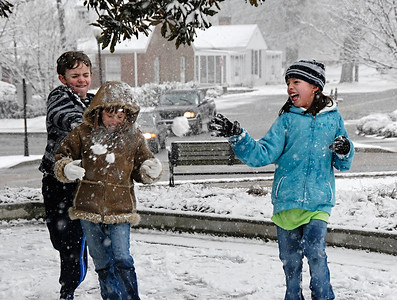 02-12-10  --snow kennesaw 01--  Zoie Olszeski, 8, of Kennesaw, in brown jacket, gets hit from both Austin Hester, 10, and Riley Lane, 9, as she tries to outrun them in the snow in downtown Kennesaw on Friday afternoon.  STAFF/LAURA MOON.