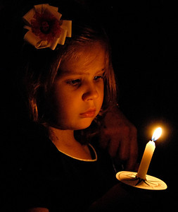 12-24-08  --christmas eve candlelight service 6--  Korey Nagel, 3, watches the glow of her candle during the candlelight service on Christmas Eve at Roswell Street Baptist Church in Marietta.  PHOTO BY LAURA MOON.