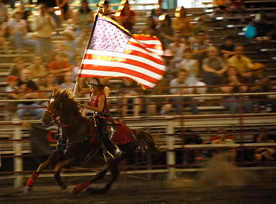 6-19-09  --rodeo 1--  Eva Horton of Atlanta carries the American flag as she rides with other members of the Ron Stone Rodeo Chicks during the opening ceremony of the Cobb County Rodeo at Jim R. Miller Park in Marietta on Friday night.  PHOTO BY LAURA MOON.