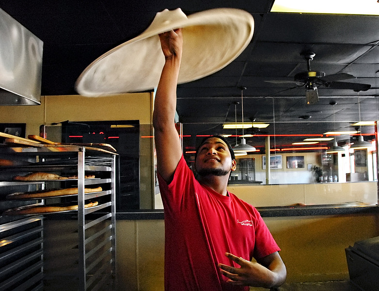 01-31-13  --baby tommys pizza 04--  Jorge Franco Guiterriez stretches out and tosses dough as he prepares a pizza at Baby Tommy's Taste of New York in Marietta.  STAFF/LAURA MOON.