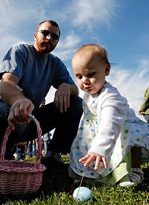 4-04-09  --feature egg hunt 5--  Lily Darrah, 1, of Acworth picks up an egg to add to her basket on Saturday morning during the Easter Egg Hunt sponsored by Freedom Church and the City of Acworth at Cauble Park.  PHOTO BY LAURA MOON.