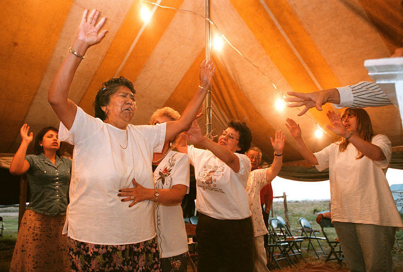 Photo by Bill Schaefer<br /> Attendees at a Friday evening tent revival gather around Thelma Jarvis, of Fort Washakie, WY., to pray for her physical and spiritual health.