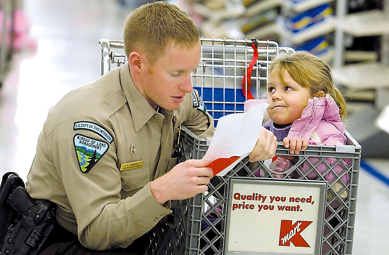 Journal photo by Bill Schaefer<br /> Law Enforcement ranger Kyle Gandiaga reads over the shopping list as Adahsia Speicher, 5, ponders what to buy for family during the Shop with a Cop Saturday morning at Kmart.
