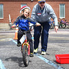 "KRISTIN BAUER / CHRONICLE <br /> Easton Cugini, 5, of Grafton, has a bit of help maneuvering his bicycle through a course from Glenn Peterson, from the Lorain County Prosecutor's Office on Sunday, April 22 during the ""Bike Rodeo"" a Bicycle Skills Clinic at North Eaton Christian Church. Students and their families were invited to partake in the event to gain bike handling skills and to learn about safe bike riding."