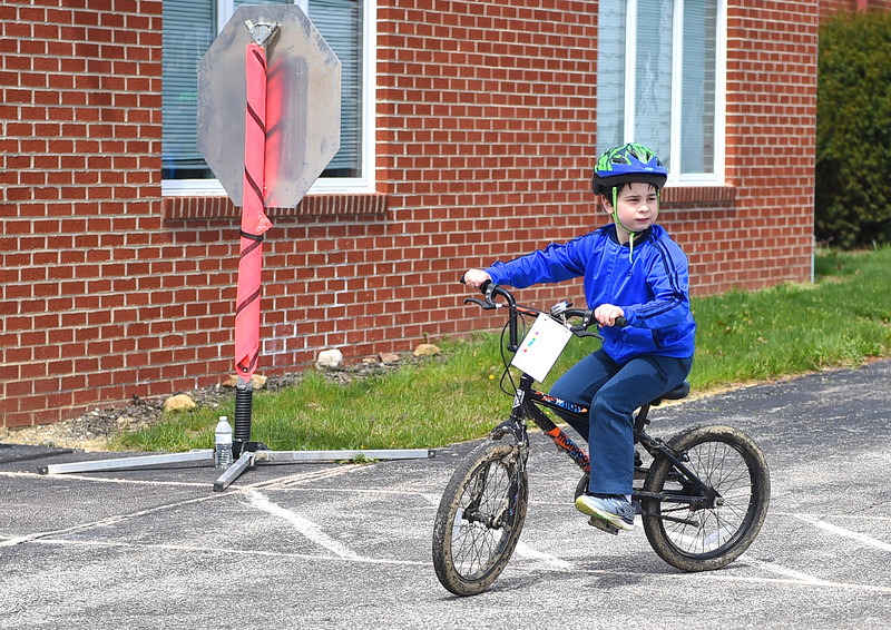 "KRISTIN BAUER / CHRONICLE <br /> Aaron Thorne, 7, of Grafton, rides his bike through the bike safety course on Sunday, April 22 during the ""Bike Rodeo"" a Bicycle Skills Clinic at North Eaton Christian Church. Police officers present were able to direct the students and teach them the proper rules and signaling to follow when riding their bikes. Students and their families were invited to partake in the event to gain bike handling skills and to learn about safe bike riding."