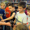 The boys take a turn touching the black king snake at Outback Ray's exotic animal show at Lagrange Public Library Sept 18.  STEVE MANHEIM / CHRONICLE