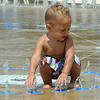 Jayce Smith, 18 months old, of Avon, plays in the water fountain at Avon Aquatic Facility on Detroit Road, Friday July 22.  STEVE MANHEIM / CHRONICLE