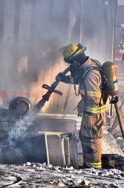 A firefighter extinguishing the burning contents of a structure fire, from the outside of the home.