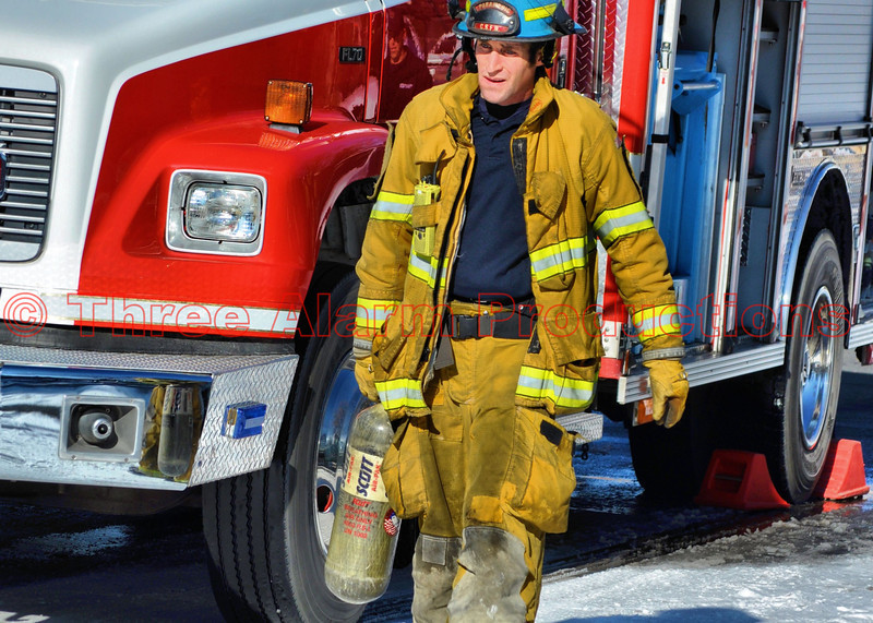 A Colorado Springs Firefighter getting an air bottle refilled on scene at a house fire.