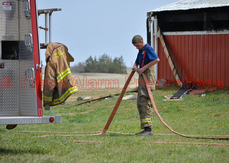 A Calhan Firefighter disassembling a hose line after fighting a barn fire.