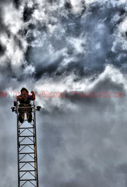 CSFD Fire Fighter that is high in the sky on a cloudy day, training near Morning Glory Garden Shop in Colorado Springs, Colorado.