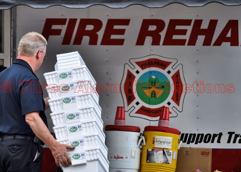 A Chaplain helping out with a stack of donated coolers to be filled with ice and bottled water for emergency personnel.