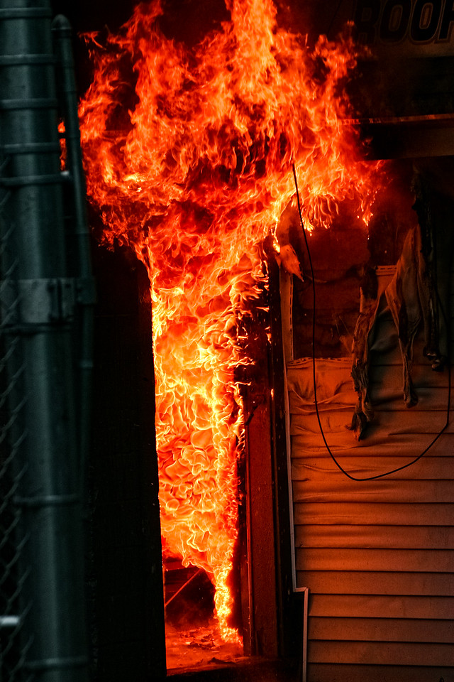 Flames shoot from a doorway at Letoile Roofing Company in Haverhill, MA.