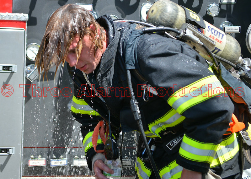 A Cimarron Hills Firefighter cooling down, after working a defensive hose line on a commercial building with heavy fire showing.