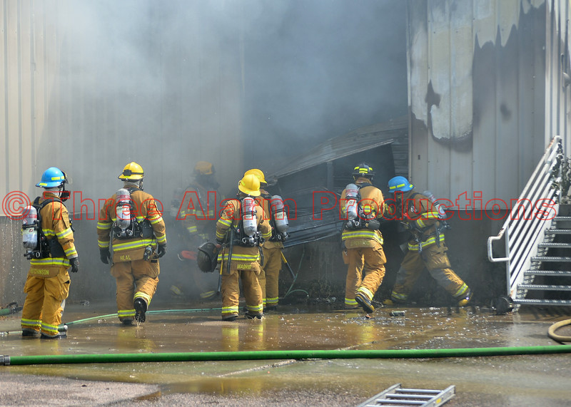Firefighters removing a rear roll-up door from the building, so they can get control of a commercial building fire in Cimarron Hills, Colorado.  August 7, 2014