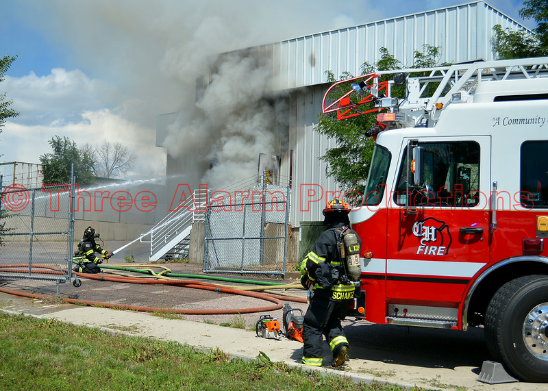 Cimarron Hills Ladder Truck 1331 and CHFD Firefighters working defensive initial fire attack lines on a commercial building with heavy fire showing on arrival at 6160 Lake Shore Court. Date of Incident: August 7, 2014