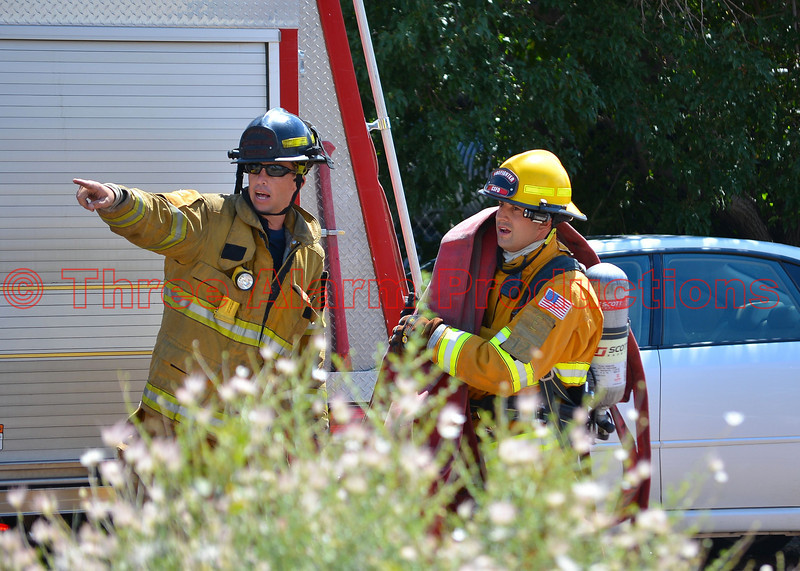 Firefighter advancing large diameter hose line on a working structure fire.