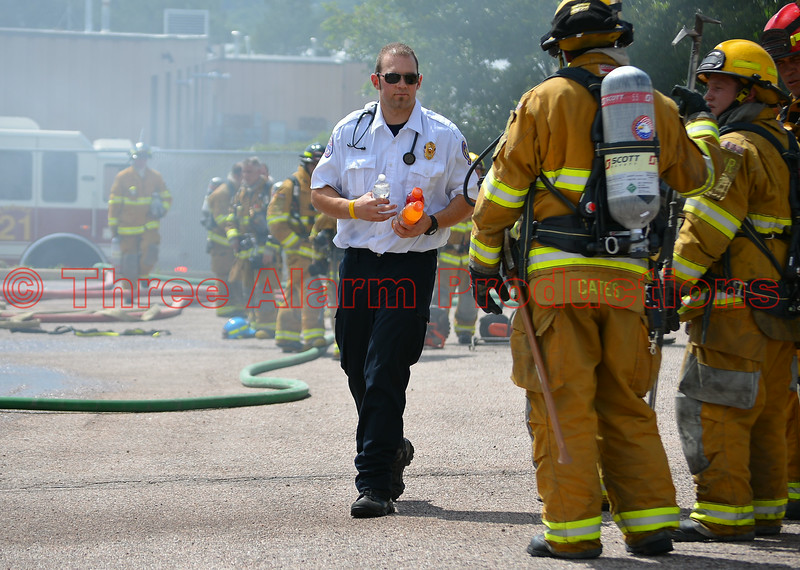 An AMR Paramedic making sure firefighters are staying hydrated at a 4-alarm fire in Cimarron Hills, Colorado.
