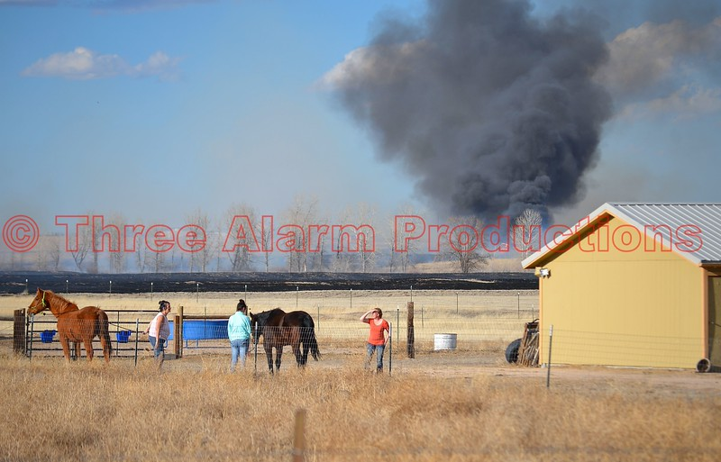 Black smoke rising from a fully involved barn during a wildland fire, in Ellicott, Colorado. March 28, 2015