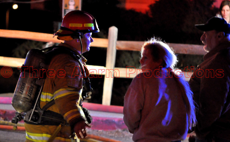 A Colorado Springs Fire Officer talking with displaced residents on a very windy night in Colorado Springs.