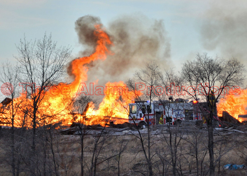 Colorado Springs Firefighters work to control a debris pile fire during 40 MPH winds, in a field at the end of Wooten Road. December 28, 2013.