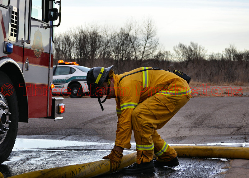 "Driver/Engineer of CSFD Fire Engine 8, getting a water supply line hooked to the pumper, on a wildland incident behind ""The Colorado Springs Flea Market."" December 28,. 2013"