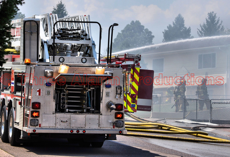Multi-agency fire crews working to bring a fully involved house fire on Viking Drive in Colorado Springs, Colorado, USA.<br /> >>><br /> On Friday, June 29, 2012, about 10:23 AM, Colorado Springs Fire Department received multiple calls about a possible house on fire on Viking Drive. The first-in company arrived about 3 minutes after being dispatched to the alarm. Fire Fighters arrived to find the home heavily involved with fire, and immediately went in a defensive mode to attack the blazing home engulfed with fire, and that was putting off a heavy plume of black smoke that could be seen easily from Peterson Air Force Base. Colorado Springs Fire Department's Lieutenant Jeff Sievers, was the on scene Public Information Officer. Lt. Sievers reported that the Fire Fighters were able to protect the homes that surrounded the blazing home and that deck gun operations were initiated early in the fire attack. Three fire engines and three ladder trucks responded. He also stated that no one was home at the time of the fire and that no injuries were reported, and that a couple of fire fighters were being monitored for possible heat exhaustion. This structure fire was upgraded to a 2-alarm fire, but did not get a usual full 2-alarm response of units, due to heavy volume of fire units on the Waldo Canyon Fire. Fire Companies from Security and Fort Carson responded to this blaze, due to filling in for local Colorado Springs Fire Stations. Lt. Sievers also said that this fire was under investigation for the cause of the fire. Resources from all over outlying fire departments are assisting Colorado Springs Fire Department with apparatus and fire fighters, due to the overwhelming demand of the Waldo Canyon Fire. The responding companies were able to get a fast and effective knock down on this blaze. Colorado Springs Police provided immediate scene security to the area. All emergency agencies were very effective in taking control of this emergency, even as resources were limited due to other fires in the region.