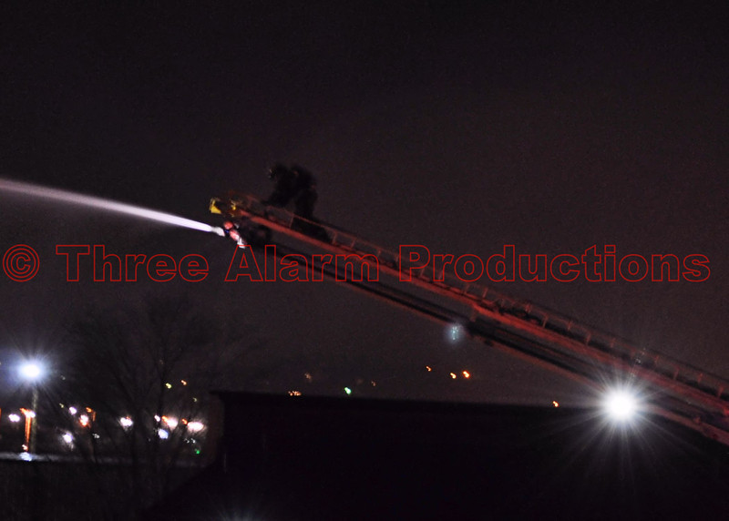 A Colorado Springs Firefighter on the ladder, of CSFD Truck 17, working a master stream in conjunction with CHFD Ladder 1331, to bring a fire under control. The blaze started in a vehicle storage lot off of U.S. Highway 24.