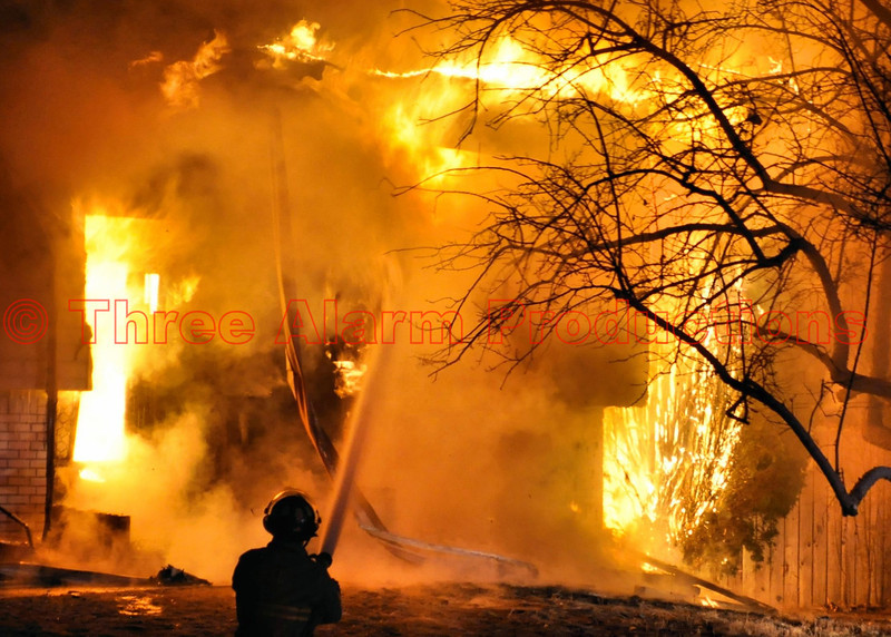"Cimarron Hills Firefighter, Dave Lancaster, working to get a knockdown on heavy flames and smoke pouring out the front (Alpha Side), of the home on Kachina Drive.<br /> <br /> On March 28, 2013, around 11PM, Cimarron Hills Fire Department was toned out for a smoke investigation on Chiricahua Drive. As emergency units were responding to that address, another address on Kachina Drive was reported to have a home with lots of smoke and flames coming out. CHFD Ladder 1331 reported lots of smoke as they approached Kachina Drive. Once on scene Ladder 31 reported heavy smoke with flames coming from a two story residential structure. Ladder 31 took a hydrant and laid out a 5inch supply line to the truck. Fire attack lines were immediately put into place, with a defensive, (exterior) mode of attack, on the burning home. The residents of the home were reported to be away. No injuries were reported from the on scene commander. Mutual aid was brought in to help control the blaze. These mutual aid emergency units were: Peterson Air Force Base Engine 9 and Chief 2, Falcon Fire Engine 313 and Brush 342, and Colorado Springs Ladder Truck 17 and Battalion Chief-District 2. The fire was brought under control with no additional structures catching fire. El Paso County Sheriff Deputies provided scene security and the Sheriff's Office dispatched an El Paso County Fire Investigator to the scene to determine the cause of the fire. The scene is under investigation at this time. No details were released on how this fire may have happened.<br /> <br /> This mentioned on Radio Reference.com at: <a href=""http://forums.radioreference.com/colorado-incidents-breaking-news/263627-el-paso-county-s-f-paged.html"">http://forums.radioreference.com/colorado-incidents-breaking-news/263627-el-paso-county-s-f-paged.html</a>"
