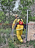 CHFD Lt. Matt Rasdall going through a break in the fence to get better access to  a wildland fire.