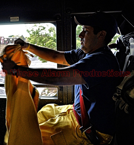 Fire Fighter Christian Herrera preparing his protective wildland gear while en route to a wildland fire aboard Cimarron Hills Fire Department's Ladder Truck 1331.