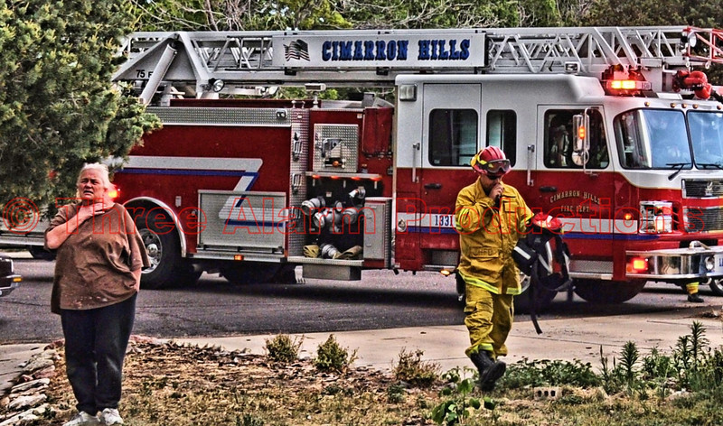 """A concerned look on a home owner's face as she looks out on a nearby wildland fire that is threatening to move into the neighborhood. Lt. Matt Rasdall arriving on the scene from Cimarron Hills Fire Department's Ladder Truck 1331.  Ladder 1331 connected to a fire hydrant with a 5 inch supply line and prepared to offer structure protection. See this area on Google Maps at: <a href=""""http://goo.gl/maps/BkpR"""">http://goo.gl/maps/BkpR</a>"""