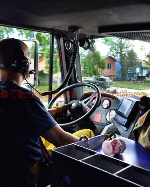 Driver, Karl Larsen, getting the crew safely to a wildland fire in Cimarron Hills Fire Department's Ladder Truck 1331 with lights and sirens on, seen heading Southbound on Peterson Road in El Paso County, Colorado.