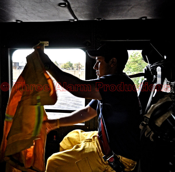 CHFD Fire Fighter Christian Herrera preparing his protective gear while en route to a wildland fire aboard Cimarron Hills Fire Department's Ladder Truck 1331.