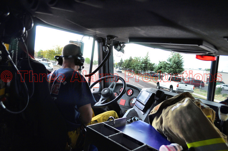 Inside the apparatus, with Driver/Engineer Karl Larsen turning onto Southbound Peterson Road to respond to a dispatched wildland fire in Cimarron Hills Ladder Truck 1331 with lights and sirens on.