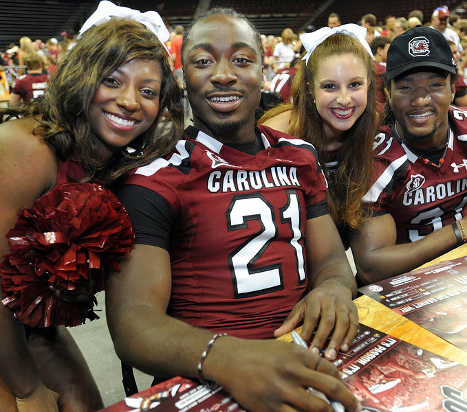 South Carolina tailbacks Marcus Lattimore, left, and Kenny Miles enjoy a pose with cheerleaders Adrienne Hinton, left, and Courtney Stoltz.<br /> South Carolina Gamecock student athletes signed autographs and posed for photos at the Colonial Life Fan Appreciation Day at the Colonial Life Arena in Columbia.<br /> GWINN DAVIS PHOTOS<br /> (864) 915-0411<br /> gwinndavis@gmail.com