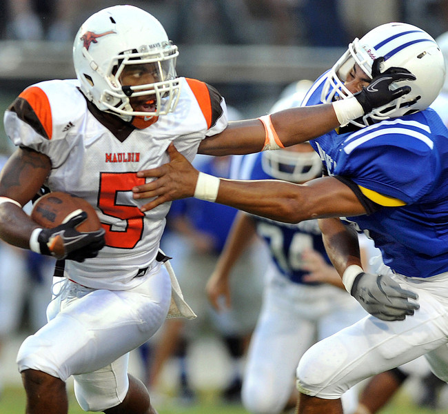 Mauldin's Reggie Lomax (5) uses the stiff arm to break free from the Woodmont defense. The Woodmont Wildcats played host to the Mauldin Mavericks in a Friday night football game.<br /> gwinn<br /> GWINN DAVIS / STAFF<br /> (864) 915-0411<br /> September 2, 2011