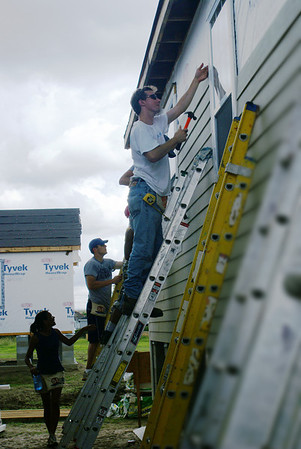 Volunteers working together siding a Habitat home.