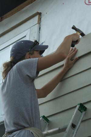 Volunteer un-nailing siding on a home.