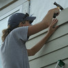 Volunteer un-nailing siding on a home.