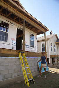 Volunteer in front of a habitat home. Another volunteer lays shingles on the roof of a home in the background.