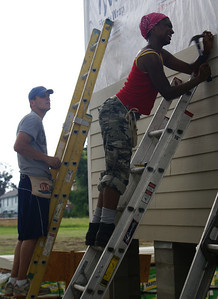 Volunteers putting up siding on a habitat home.
