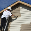 Just one of many Entergy volunteers, painting the side of a home.