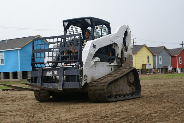 A Happy bobcat driver,drives by a row of colorful habitat homes.