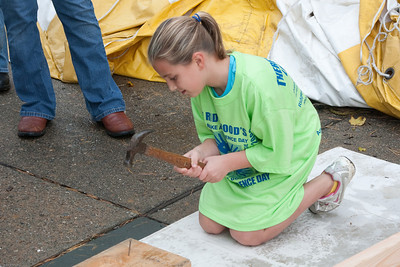 (1) Pslip Slug #: W 25054; (2) Ridgewood, NJ; (3) 10/24/09; (4) Habitat for Humanity Builds a House for Make a Difference Day on 10/24/2009; (5) Mike Megnin holds pieces steady for Lauren during Habitat for Humanity's group build during Ridgewood's Make a Difference Day on 10/24/2009; (6) W.H. Grae for the Ridgewood News.
