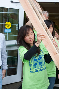 (1) Pslip Slug #: W 25054; (2) Ridgewood, NJ; (3) 10/24/09; (4) Habitat for Humanity Builds a House for Make a Difference Day on 10/24/2009; (5)  Soobin Chang leads the way as another completed panel built by Habitat For Humanity volunteers emerges from the Community Center during Ridgewood's Make a Difference Day on 10/24/2009; (6) W.H. Grae for the Ridgewood News.