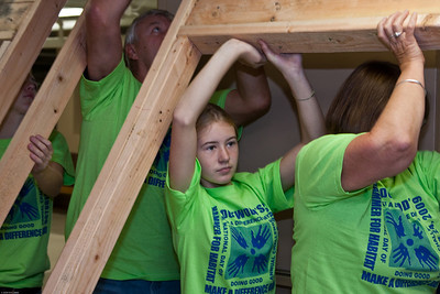 (1) Pslip Slug #: W 25054; (2) Ridgewood, NJ; (3) 10/24/09; (4) Habitat for Humanity Builds a House for Make a Difference Day on 10/24/2009; (5)  Caiti Hensley helps bring out another panel during Habitat for Humanity's project during Ridgewood's Make a Difference Day on 10/24/2009; (6) W.H. Grae for the Ridgewood News.
