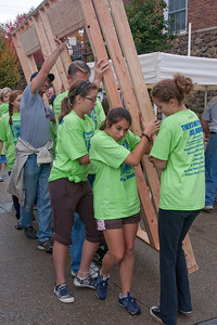 (1) Pslip Slug #: W 25054; (2) Ridgewood, NJ; (3) 10/24/09; (4) Habitat for Humanity Builds a House for Make a Difference Day on 10/24/2009; (5)  Laura Johnson, Riley Mulligan and Simone Bontoux (L-R) lead the rest of the crew bringing out the first complete panel during Habitat for Humanity's project at Ridgewood's Make a Difference Day on 10/24/2009; (6) W.H. Grae for the Ridgewood News.