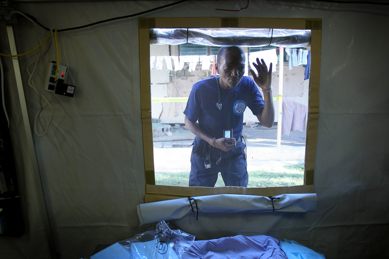 1/21/10 Port au Prince, Haiti  -  Dr. Thea James, an emergency room doctor at Boston Medical Center, peaks in the operating room tent to see the action inside. Thursday turned out to be a busy day at the DMAT/IMSuRT hospital near Tent City in Port-au-Prince, Haiti. Another 4.7 earthquake, a medical emergency within the DMAT team and a steady stream of patients kept the medical staff and journalists busy.   Story by Stephen Smith/Globe Staff. Dina Rudick/Globe Staff.